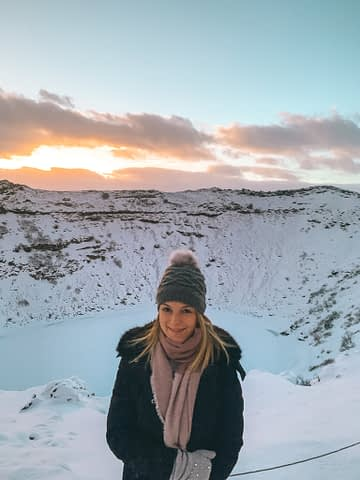 A snowy Kerid crater with a colourful skyline as part of the golden circle tour in Iceland.