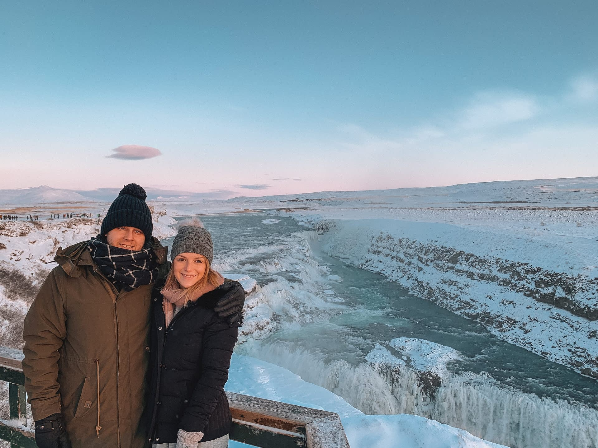 A couple stood in front of Gullfoss waterfall. Golden Circle tour as part of what to do in Iceland