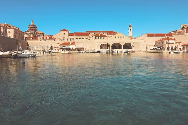A view of the ocean and boats with red roof houses in the background. What to do in Dubrovnik.