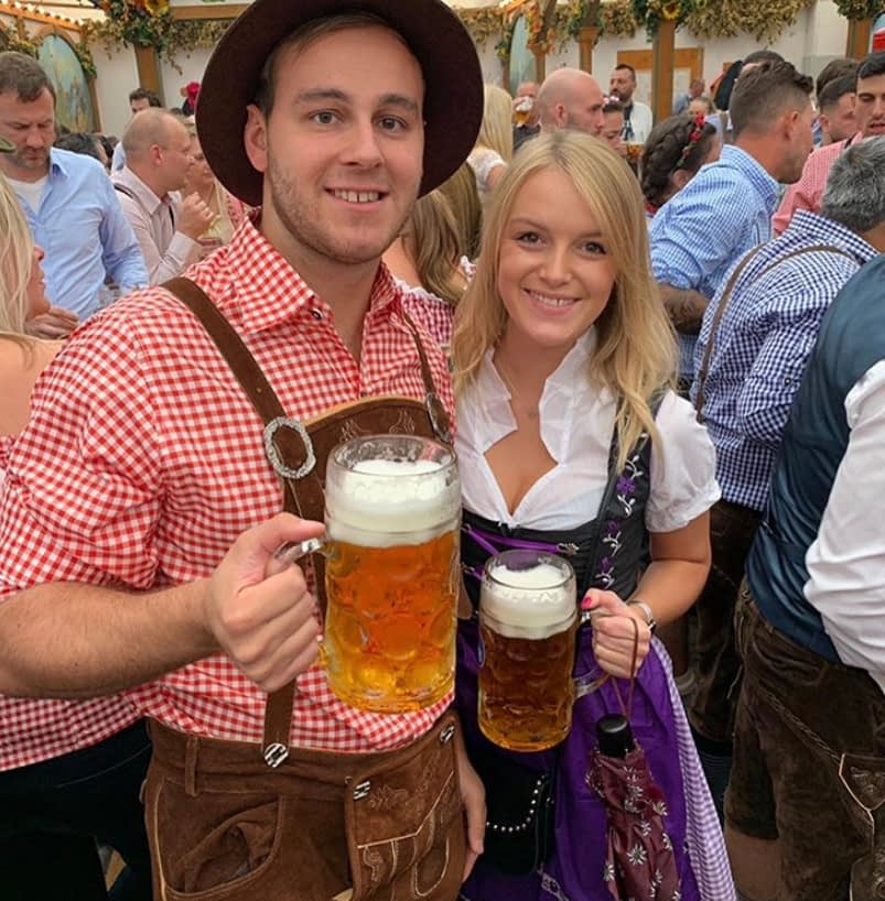 A couple in Bavarian outfits with beer
