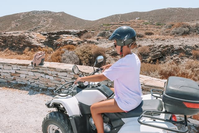 A woman on an ATV in Ios. How to get about in Ios