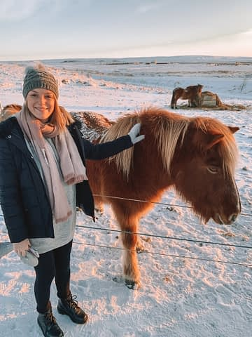 A woman with a brown, Icelandic horse. Lots of snow around. What to do in Iceland