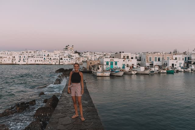 A woman stood on a sea breaker next to a harbour. Things to do in Paros