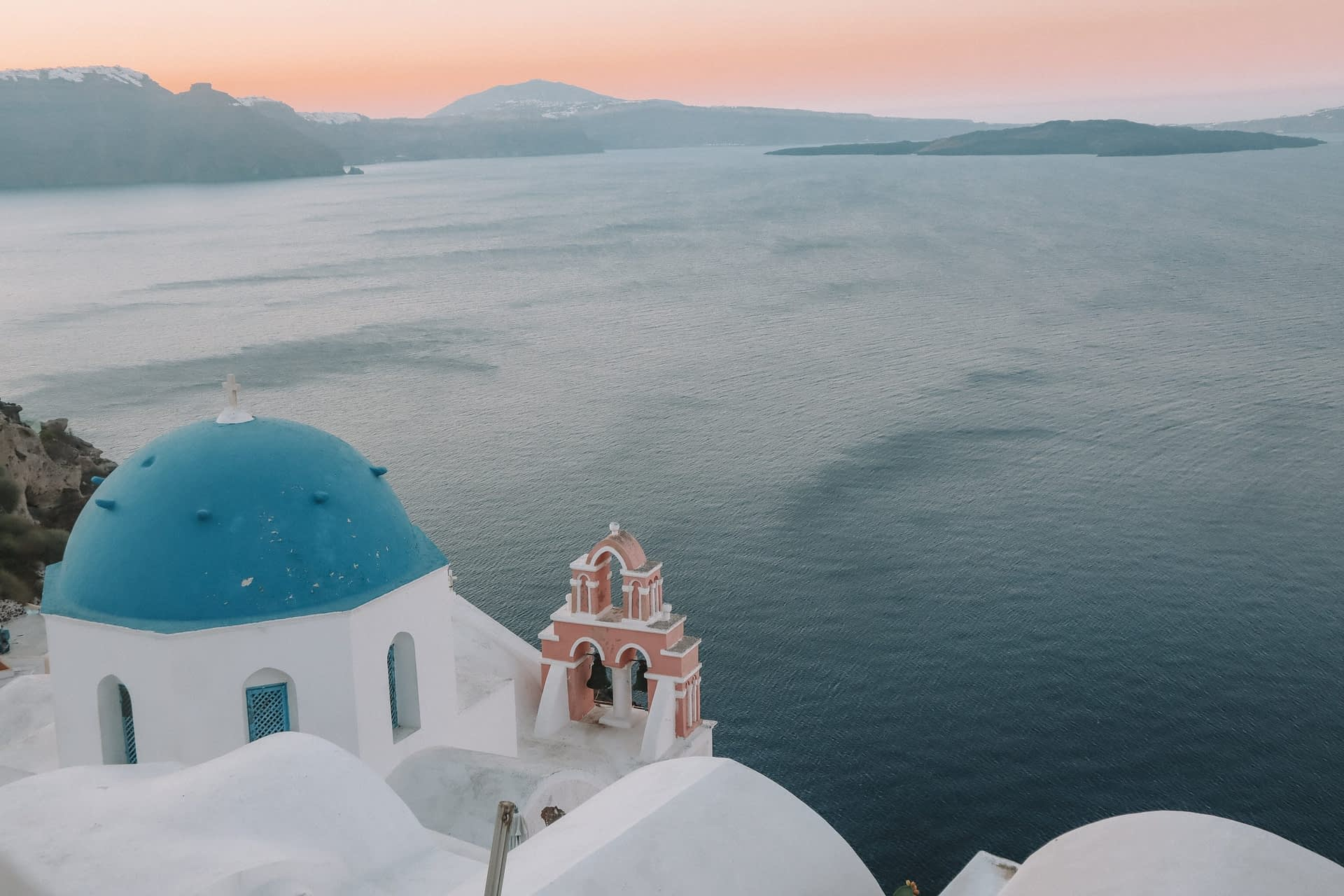 A view of the islands, blue domed church of Oia during sunrise