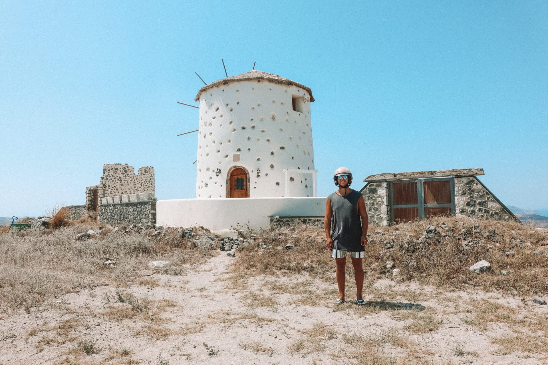 A white windmill on sparse land. What to do in Santorini