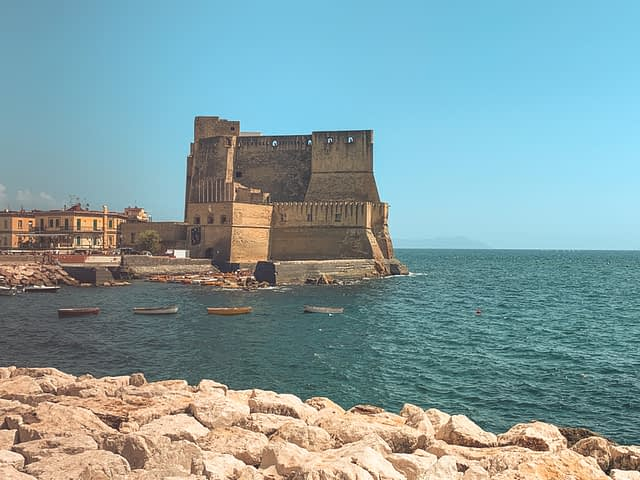 Naples castle with colourful buildings nearby. Things to do in Naples