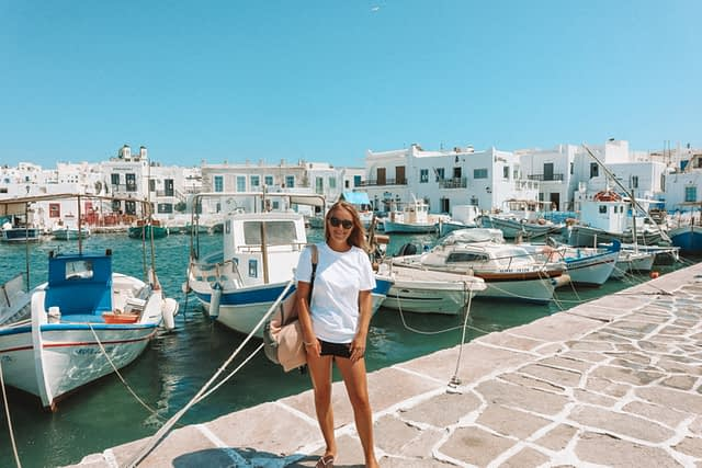 A woman stood infront of boats and whitewashed houses in Naoussa, Paros.