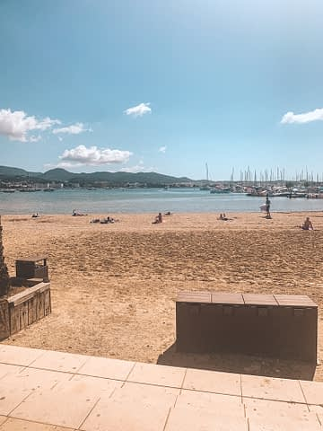 Becachfront with ocean and boats and some clouds. Things to do in Ibiza on a budget.