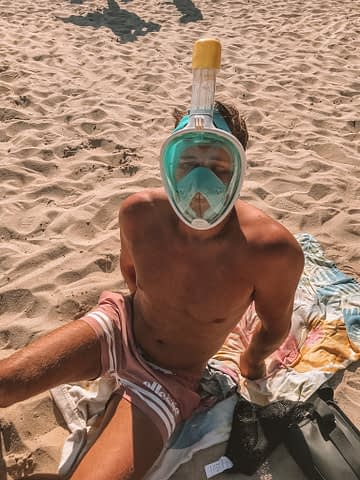 A man wearing a full face snorkel mask on a beach in Sardinia