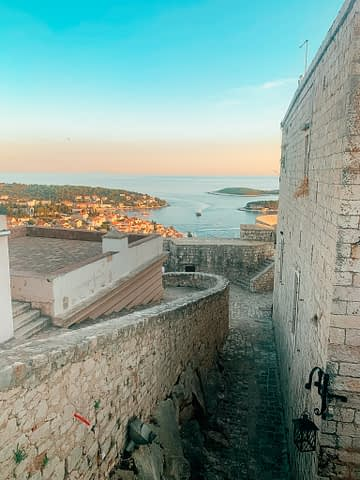 Castle walls with Hvar old town, ocean, boats and islands in the turquoise background. What to do in Hvar