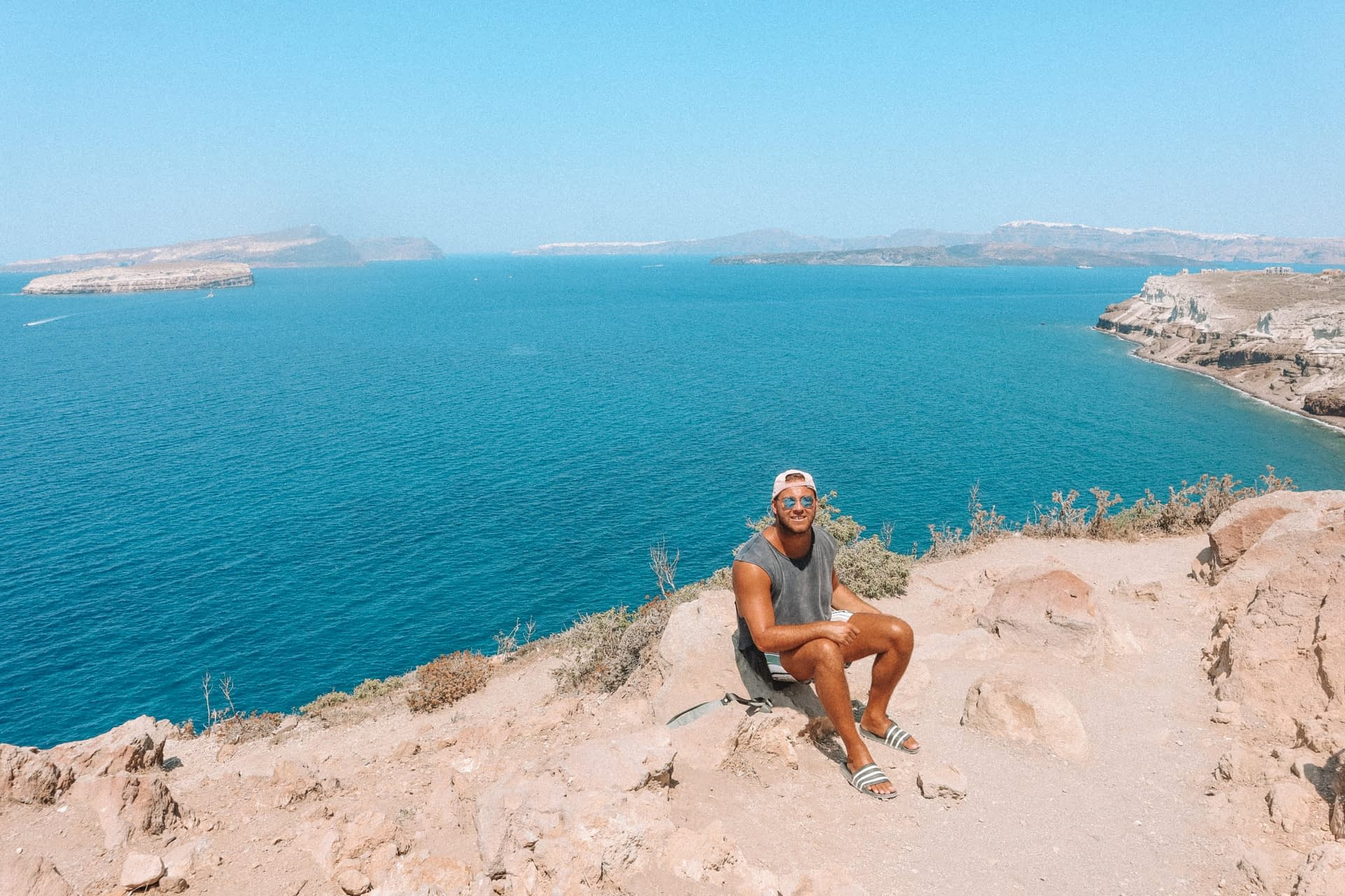 A man sat on rocks around the coastline next to the turquoise waters.