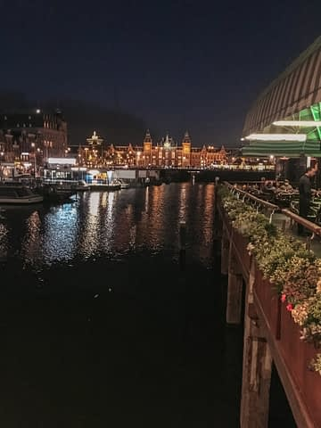 A view of the Amsterdam train station at night across the water. Amsterdam on a budget