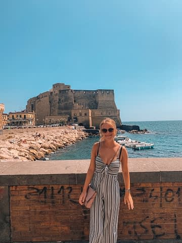 A woman posing next to graffiti and Naples castle. Where to go in Naples