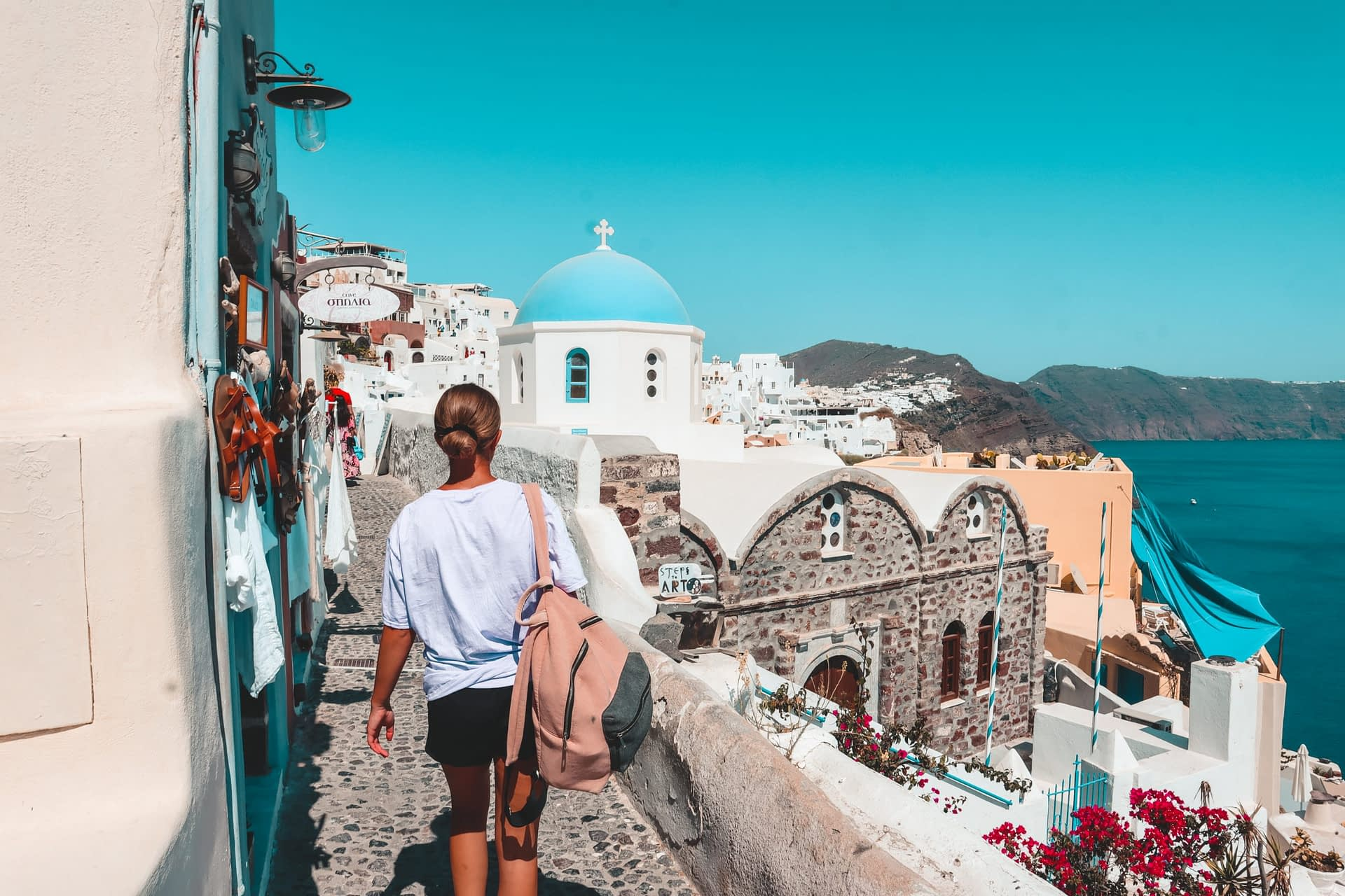 A woman strolling around the streets of Oia. Things to do in Oia