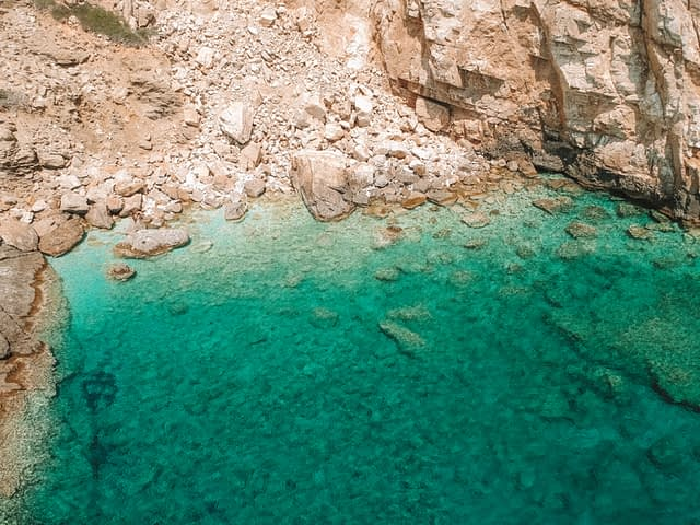 Green, turquoise sea at Never Bay rocks. Ios travel blog