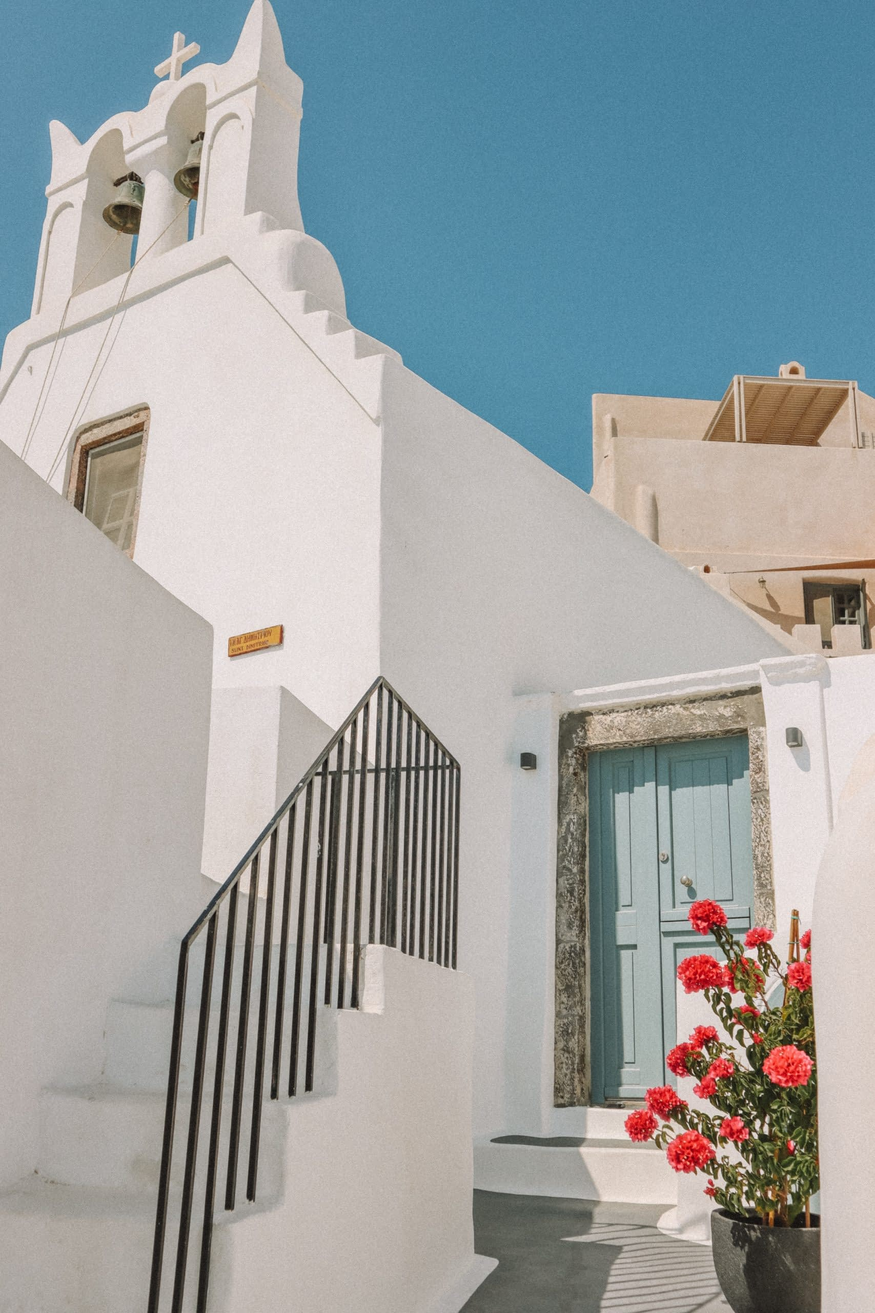 A whitewashed building with flowers and a blue painted door. Things to do in Santorini