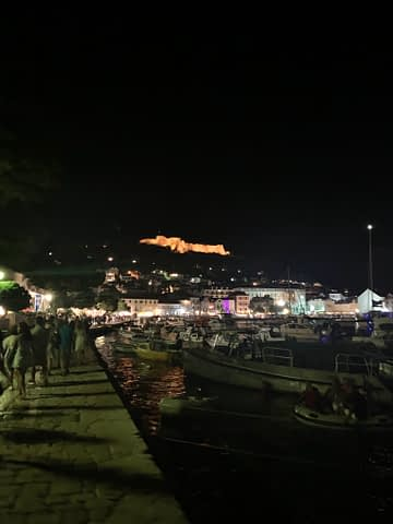 Hvar old town and harbour at night with a lit up castle in the background. Things to do in Hvar
