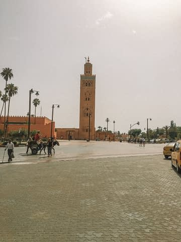 A tall tower near palm trees in Marrakech. Morocco Travel guide