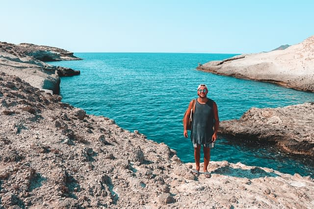 A man infront of turquoise water at Kapros beach