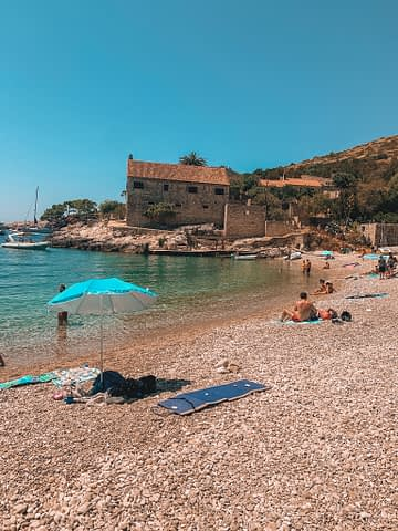 A pebble beach with turquoise water and an old building nearby