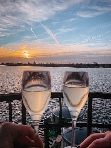 The sun setting in the background, near the sea and a picture two glass of champagne. Things to do in Copenhagen