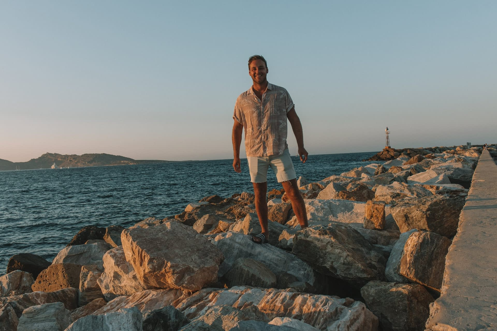 A man stood on the rocks during sunset at Naoussa harbour. Things to see in Paros