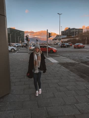 A woman in Reykjavik with the Harpa Concert Hall in the background as part of the things to do in Reykjavik, Iceland.