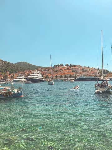 A harbour with boats and colourful buildings in the background. What to do in Hvar