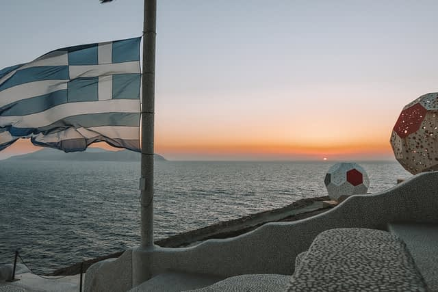 A greek flag with the sun setting in the background. Ios travel blog, pathos lounge