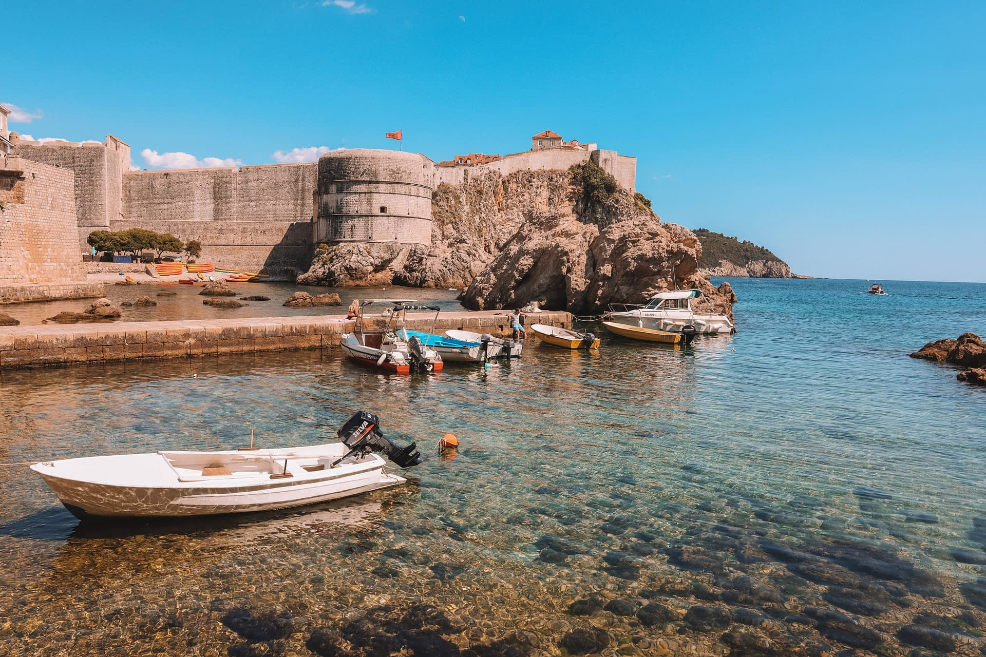 Boats in the ocean and a castle in the background. What to do in Dubrovnik.