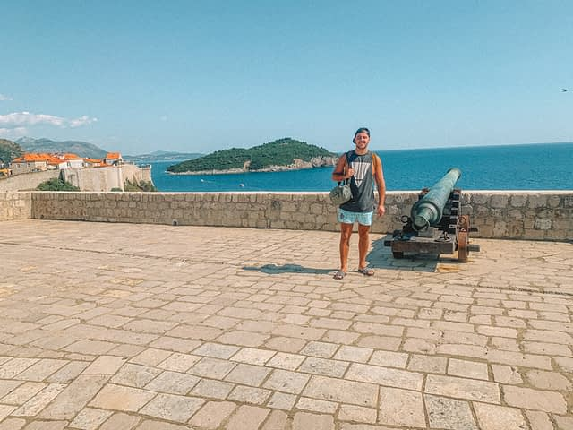 A man stood next to a cannon on top of Lovrijenac fort