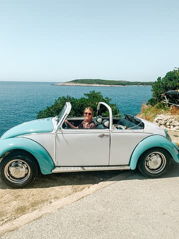 A woman in a 60's white and blue VW convertible with the sea in the background. What to do in Hvar