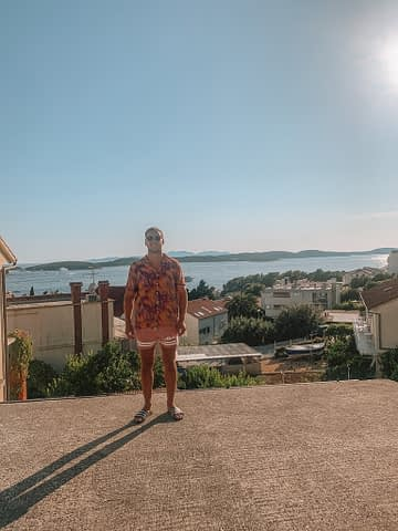 A man stood at a viewpoint with islands and the ocean in the background. Things to do in Hvar