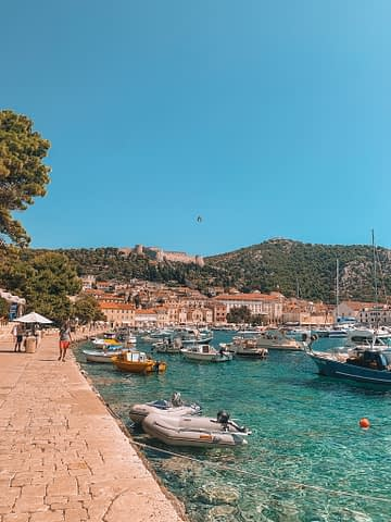 Hvar harbour with the old town, boats and a castle on a hill. Things to do in Hvar