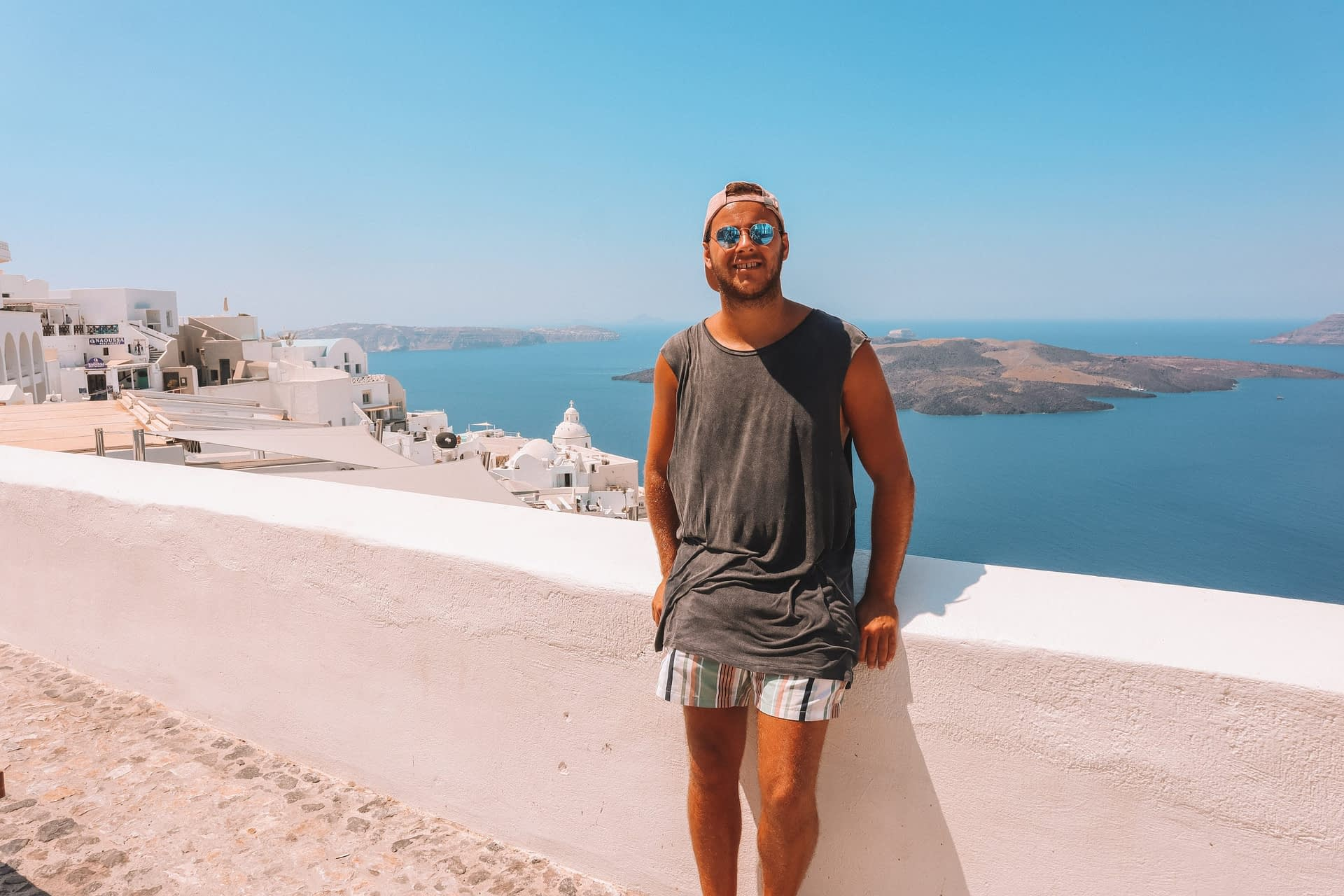 A man sat on a wall with islands in the background of Thira, Santorini