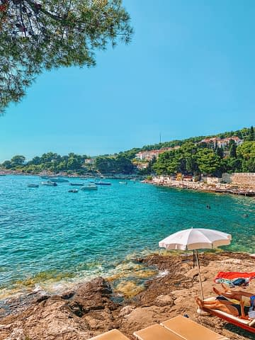 A beach in Hvar with an umbrella and turquoise ocean. What to do in Hvar
