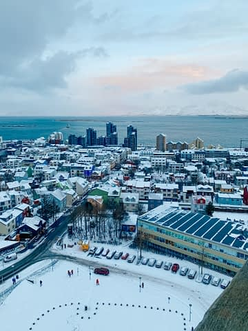 Aerial view of Reykjavik,Iceland in snow. Budget travel idea where you can see buildings and mountains from the Hallgrimskirkja church. Where to stay in Reykjavik