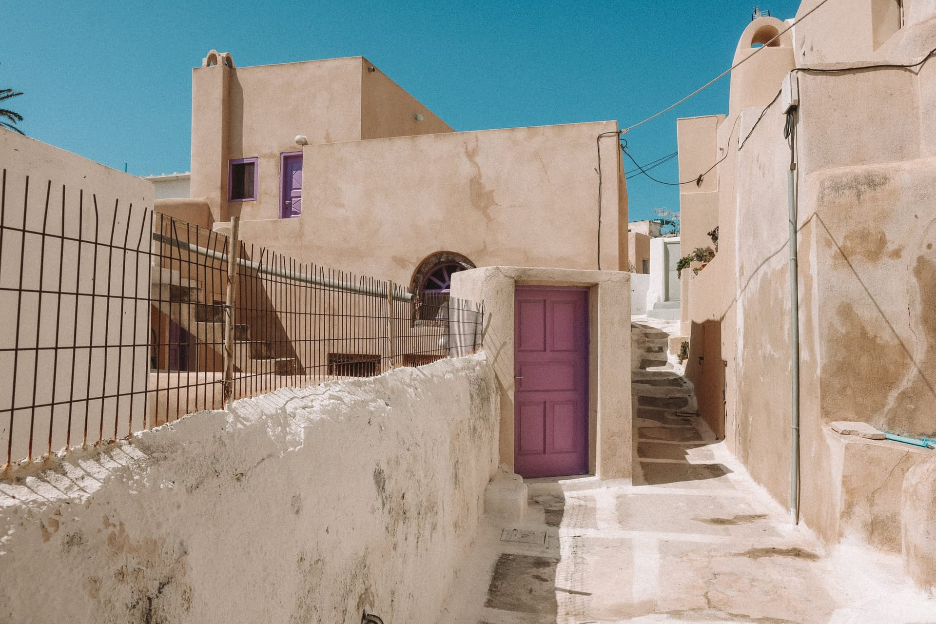 Village alleyway in Emporio with peach washed houses and purple doors. Things to do in Santorini