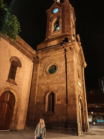 A woman stood in front of a church at night. Where to stay in Tenerife