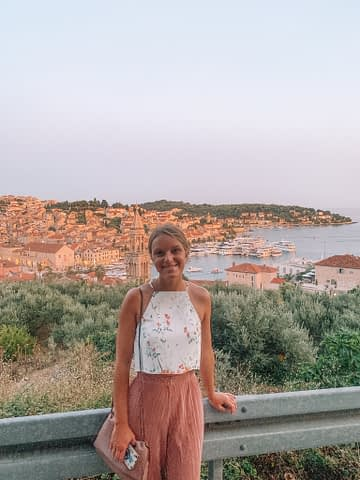 A woman stood with a view of Hvar near the castle. A church and the old town and ocean can be seen.