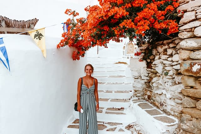 A woman stood in the Chora streets in Ios with flowers in the background. Things to do in Ios