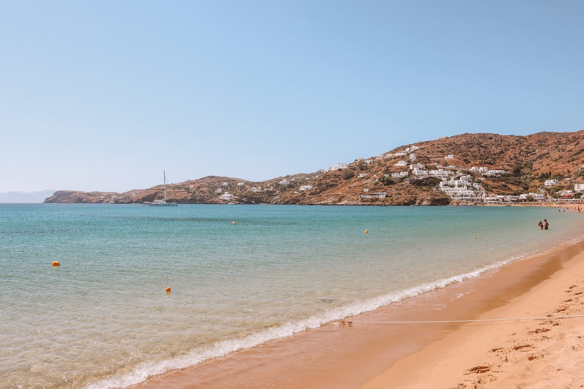 Mylopotas beach from the side with whitewashed houses in the background. Best beaches of Ios