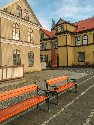 Colourful buildings in Iceland with two benches. What to do in Iceland