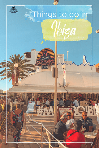 Cafe Mambo in San Antonio with palm trees and people and a blue sky. Things to do in Ibiza on a budget.