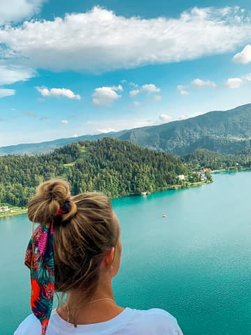 A woman looking at Lake Bled from the castle. What to do in Lake Bled
