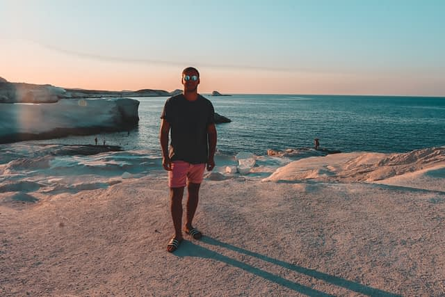 A man stood in front of the Sarakiniko rocks during sunset
