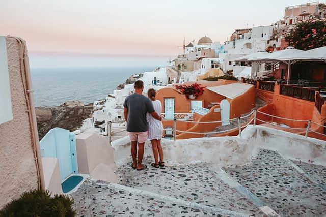 A couple looking out to sea with the pastel buildings in Oia in the view