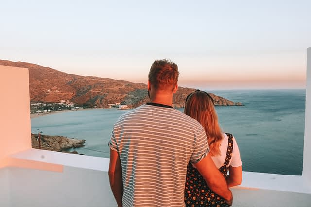 A couple looking at Mylopotas beach in Ios with the ocean in the background. Where to stay in Ios