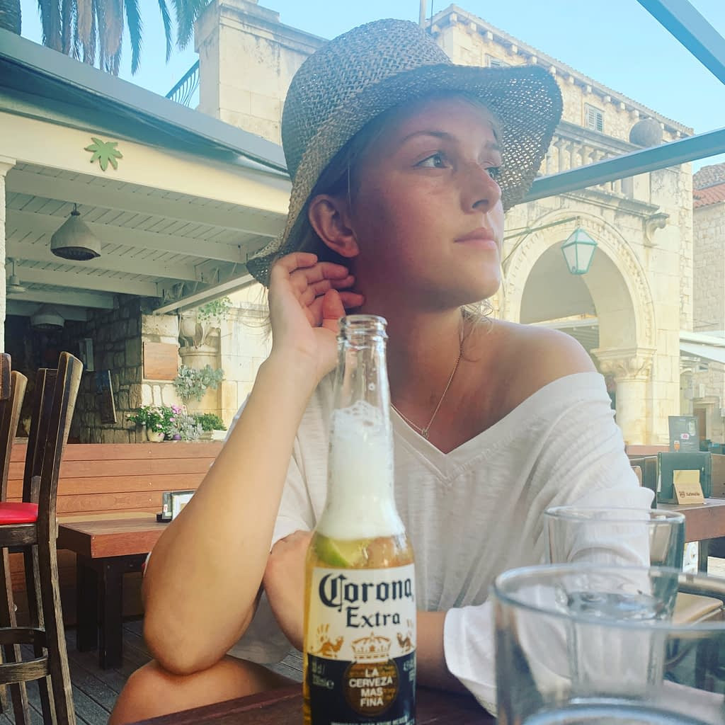 A woman with a hat on with a bottle of beer