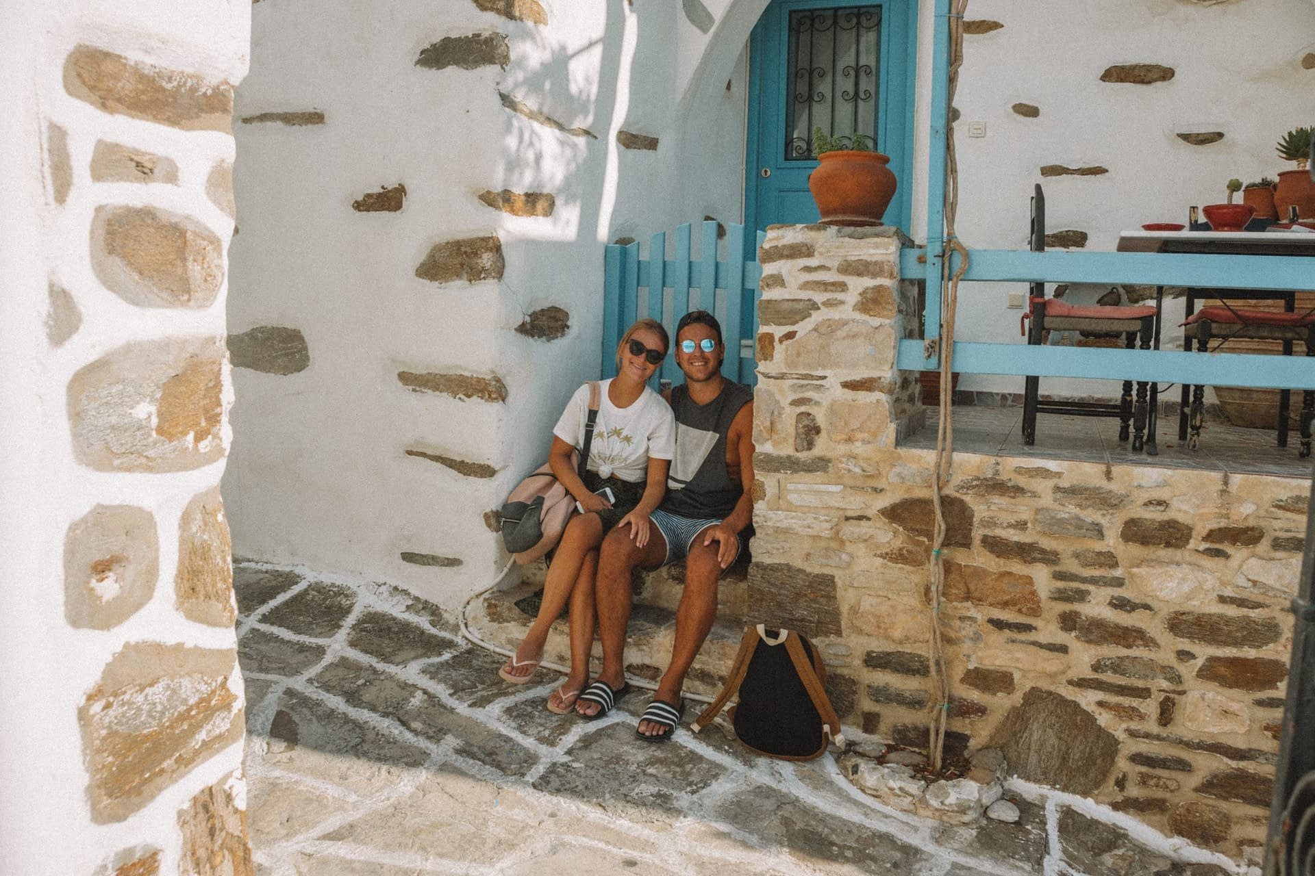 A couple sat in front of a Lefkes village house. Things to see in Paros